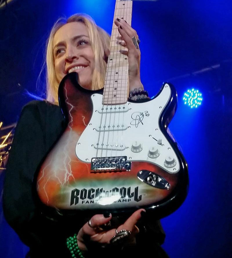 Woman on stage, holding a custom, autographed Rockcamp guitar